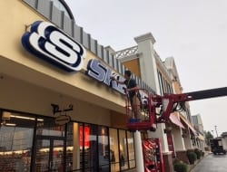 Servicing and cleaning Sketchers store front sign